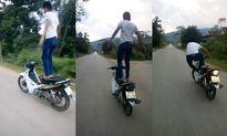 Clip đứng trên yên xe máy chạy vù vù trên đường